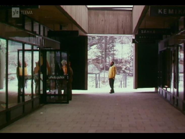 Mies seisoo ympärilleen katsellen ostolan ulkokäytävän päässä