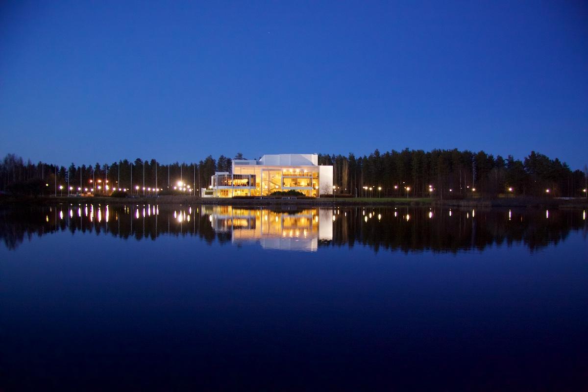 Valkea sisältä valaistu konserttitalo sinisessä iltahämyssä lammen rannalla