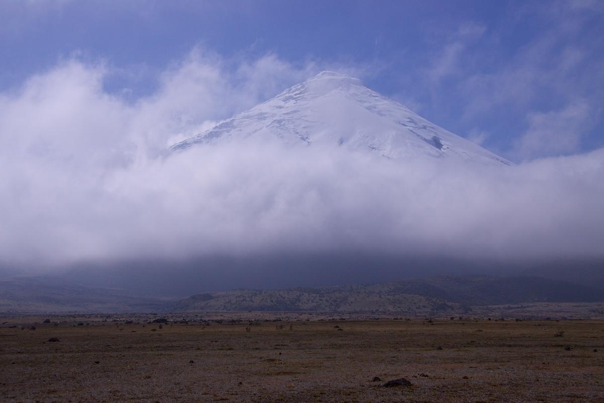 Valkea kartiomainen tulivuori pilviharson takana ruskean tasangon tuolla puolen