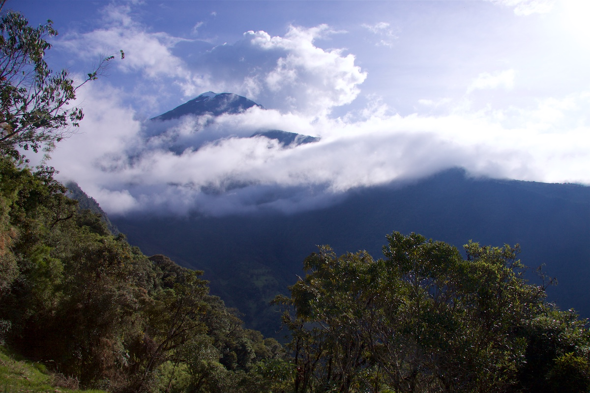 Pilvien lomassa vuoren huippu, edessä puustoisia kukkuloita