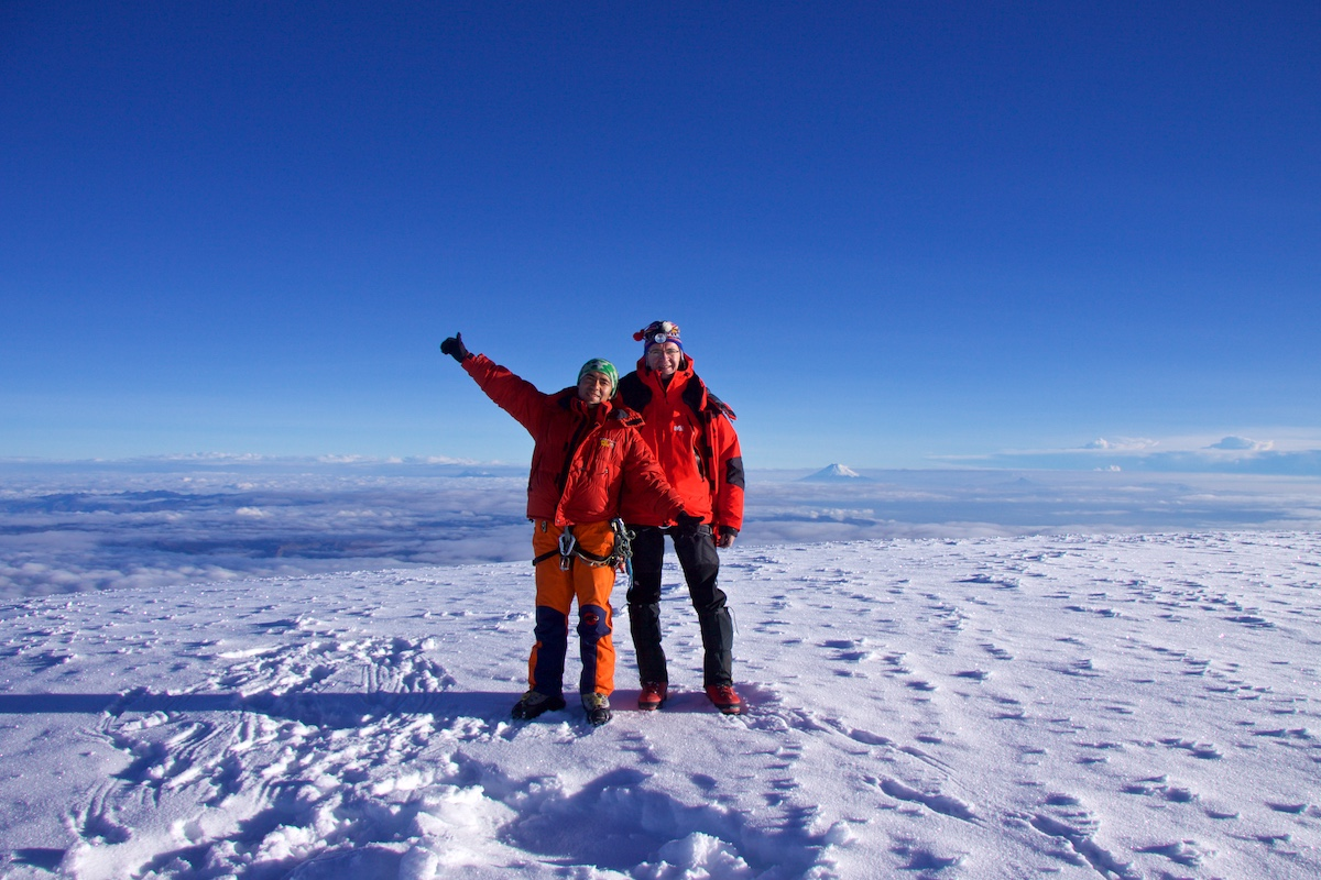 Kaksi kiipeilijää poseeraa tasaisella lumisella vuorenlaella.