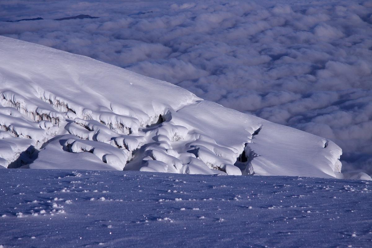 Vuorenhuipun jäätikkö pilvien yläpuolella