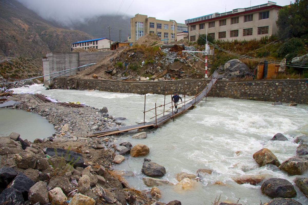Tilapäinen kävelysilta kuohuvan joen yli kaupungin reunalla sumuisten vuorten juurella