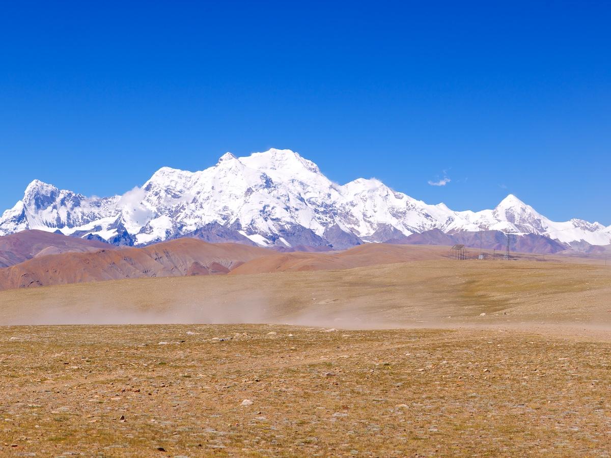 Valtava valkoinen vuoriryhmä ruskeiden kukkuloiden takana