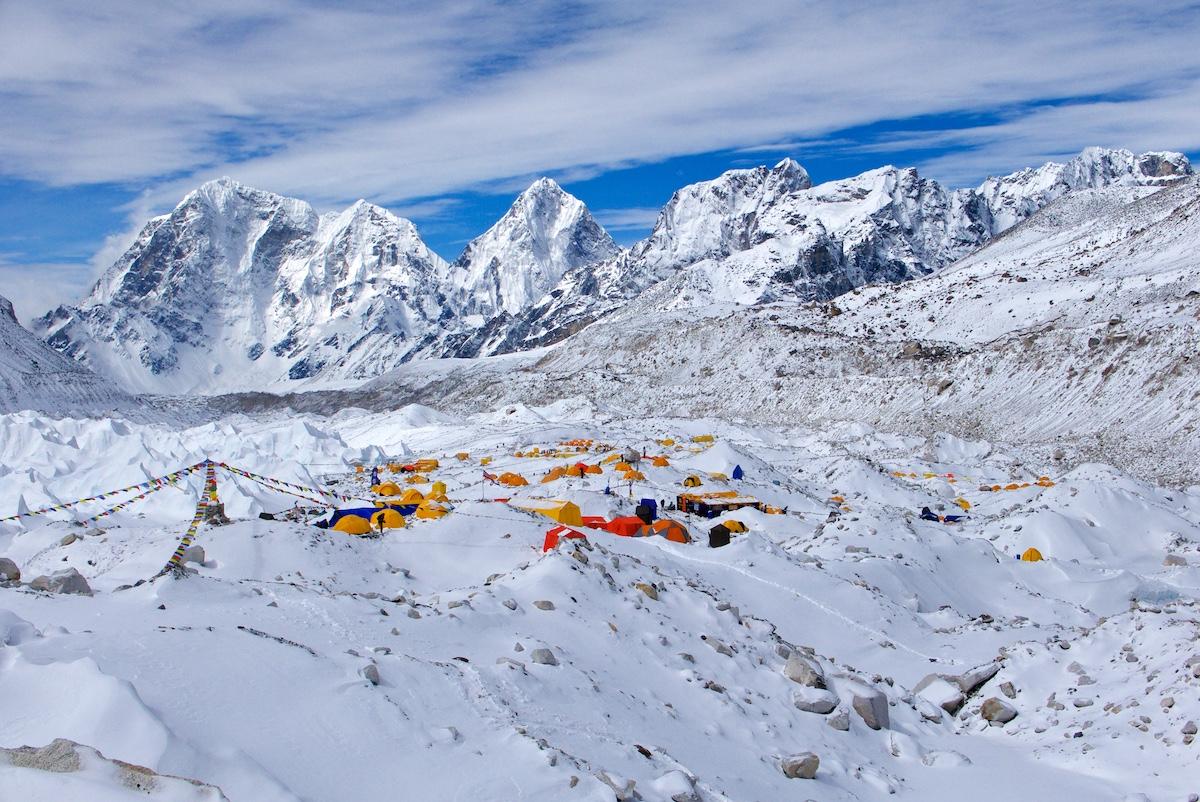 Telttoja jäätiköllä, vuoria taustalla