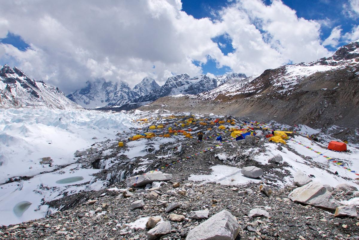 Satojen eriväristen telttojen leiri jäätikön moreenilla vuorimaisemassa