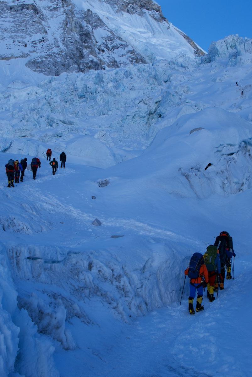 Kiipeilijäryhmät nousevat aamuhämärässä jääputoukseen