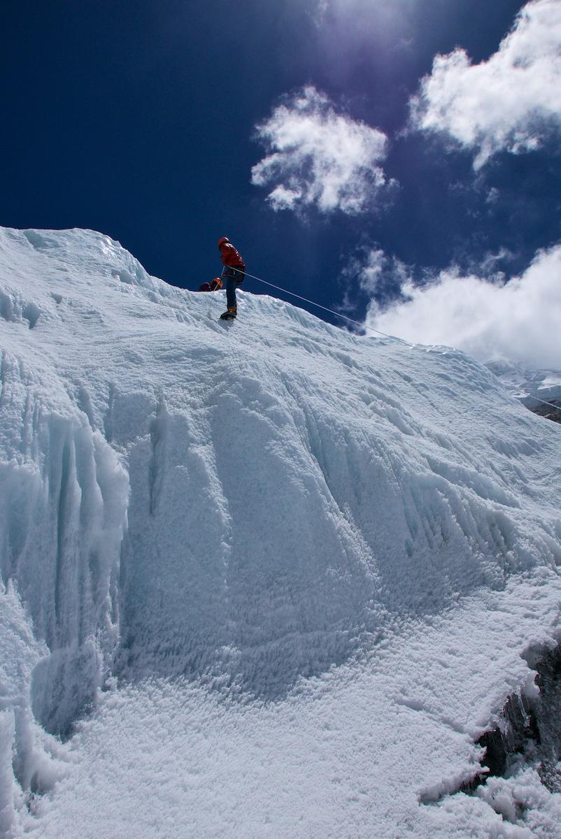 Kiipeilijä nousee jäätornin huipulle.