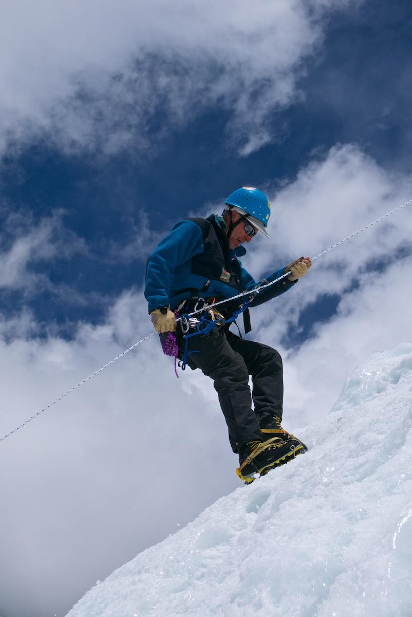 Kiipeilijä laskeutuu köydellä jääseinämää
