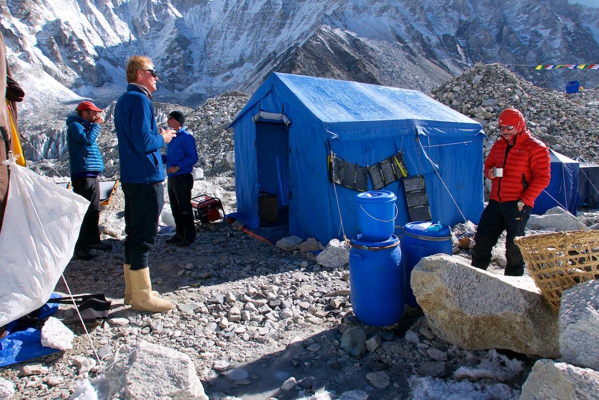 Kiipeilijät juovat teetä ruokailuteltan edessä.