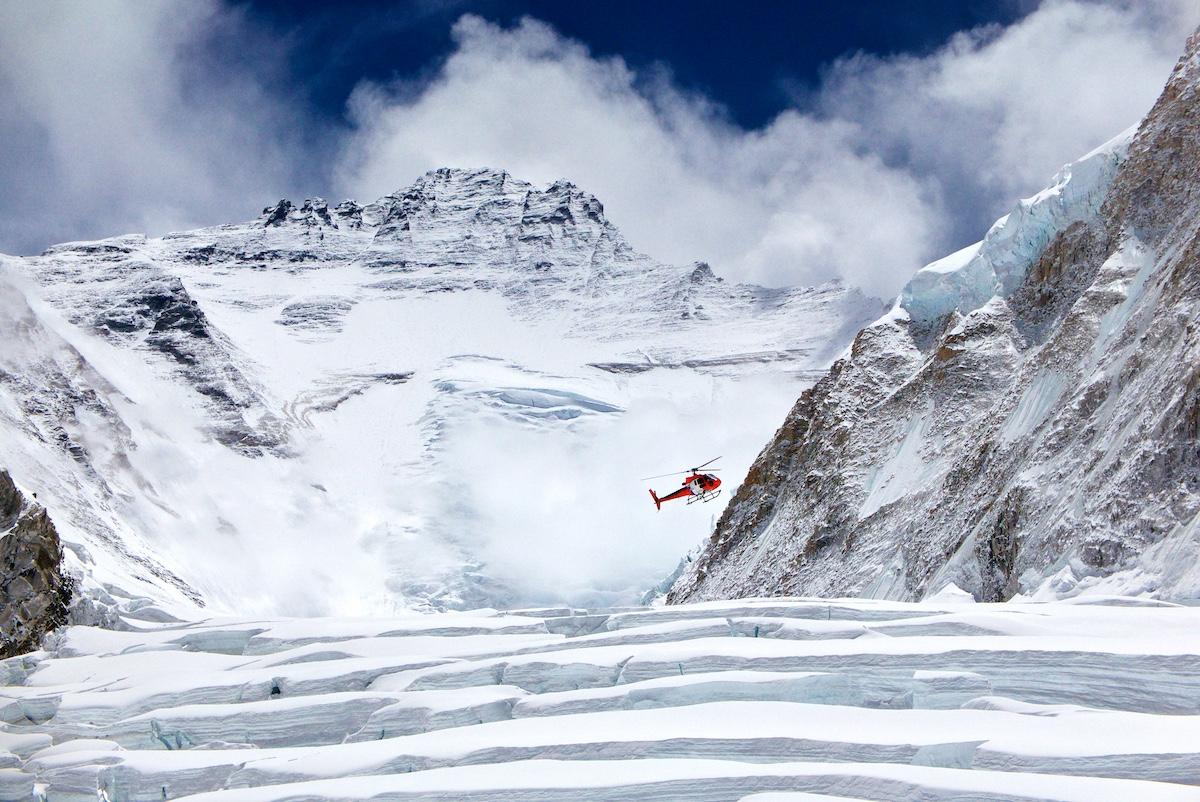Helikopteri lentää korkeiden vuorenhuippujen ympäröimässä jäätikkölaaksossa