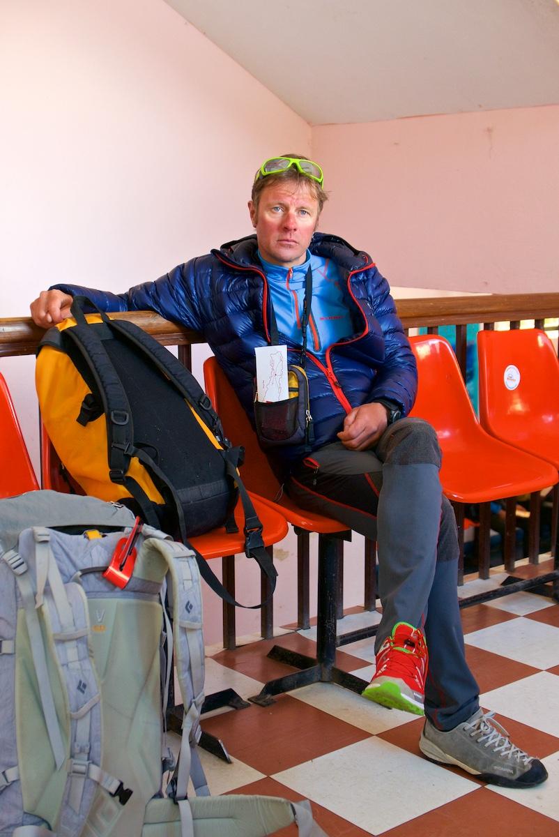 Eriparikenkäinen kiipeilijä istuu odotussalissa.