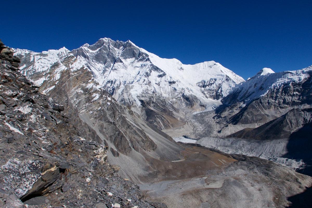 Korkea lumipeitteinen vuori, jäätikkölaaksoja ja kivisiä harjanteita