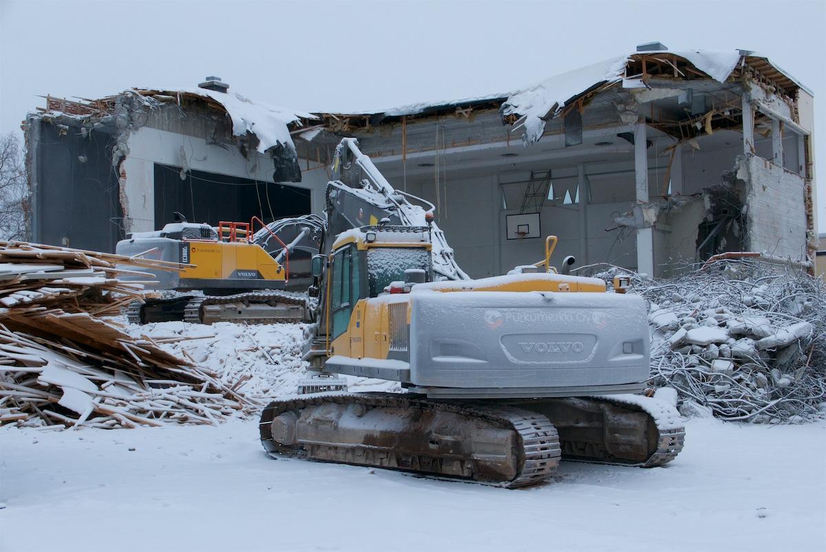 Puoliksi purettu koulun voimistelusali ja kaksi kaivinkonetta