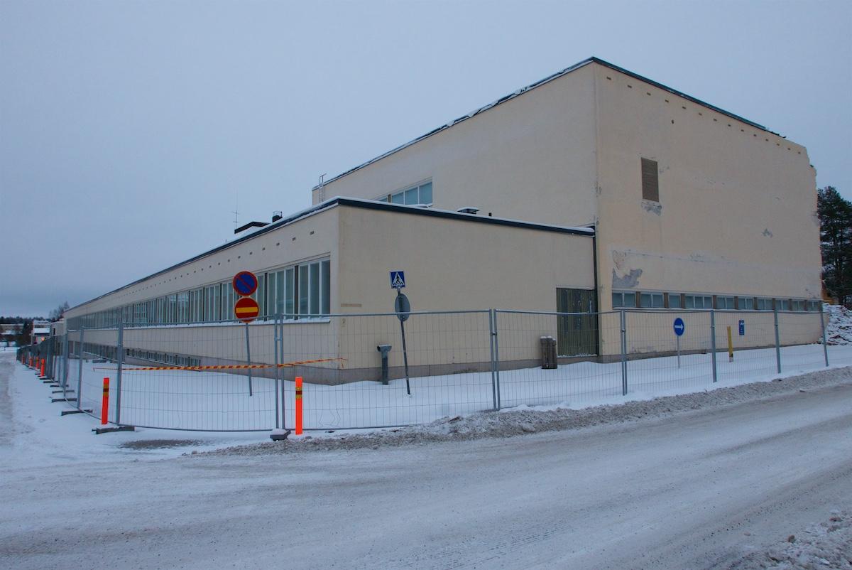 Koulurakennus on ympäröity aidalla kadun puolelta.