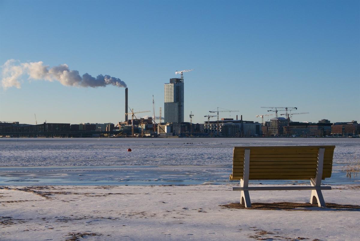 Hiekkaranta ohuen lumen peitossa, tyhjä penkki, vastarannalla rakenteilla oleva pilvenpiirtäjä