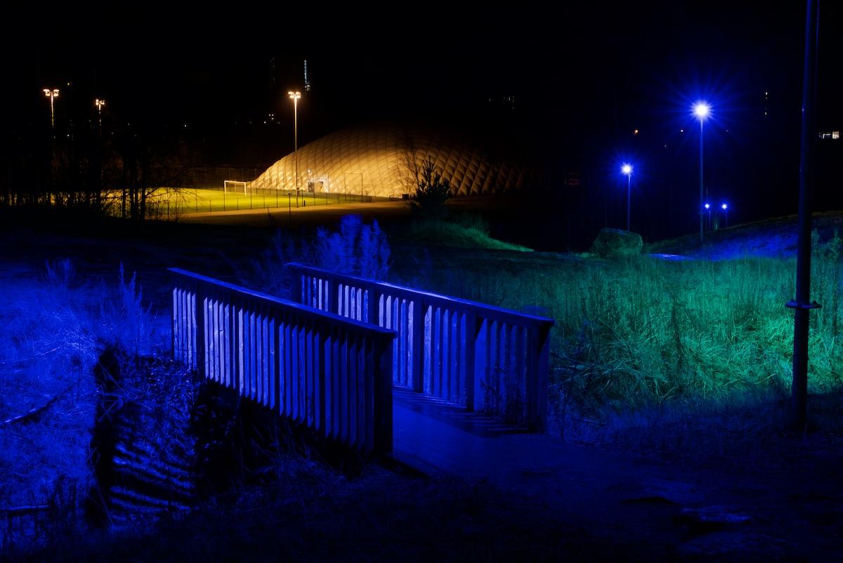 Siniseksi valaistu kävelysilta, heinikkoinen purouoma ja taustalla oranssissa natriumvalossa kiiltävä kuplahalli ja urheilukenttä