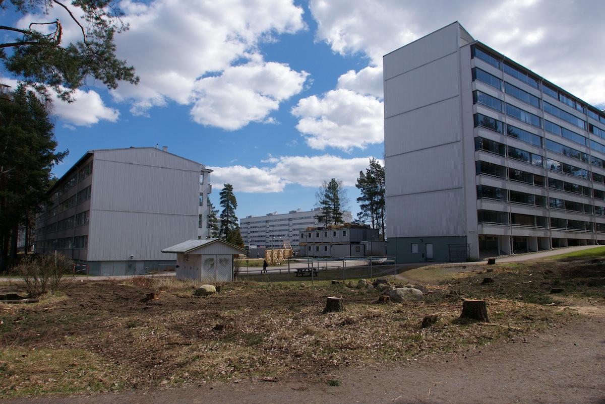 Isojen kerrostalojen päädyt raajaavat kulma-aluetta, josta on puut kaadettu. Taustalla kerrostaloja ja työmaaparakkeja.