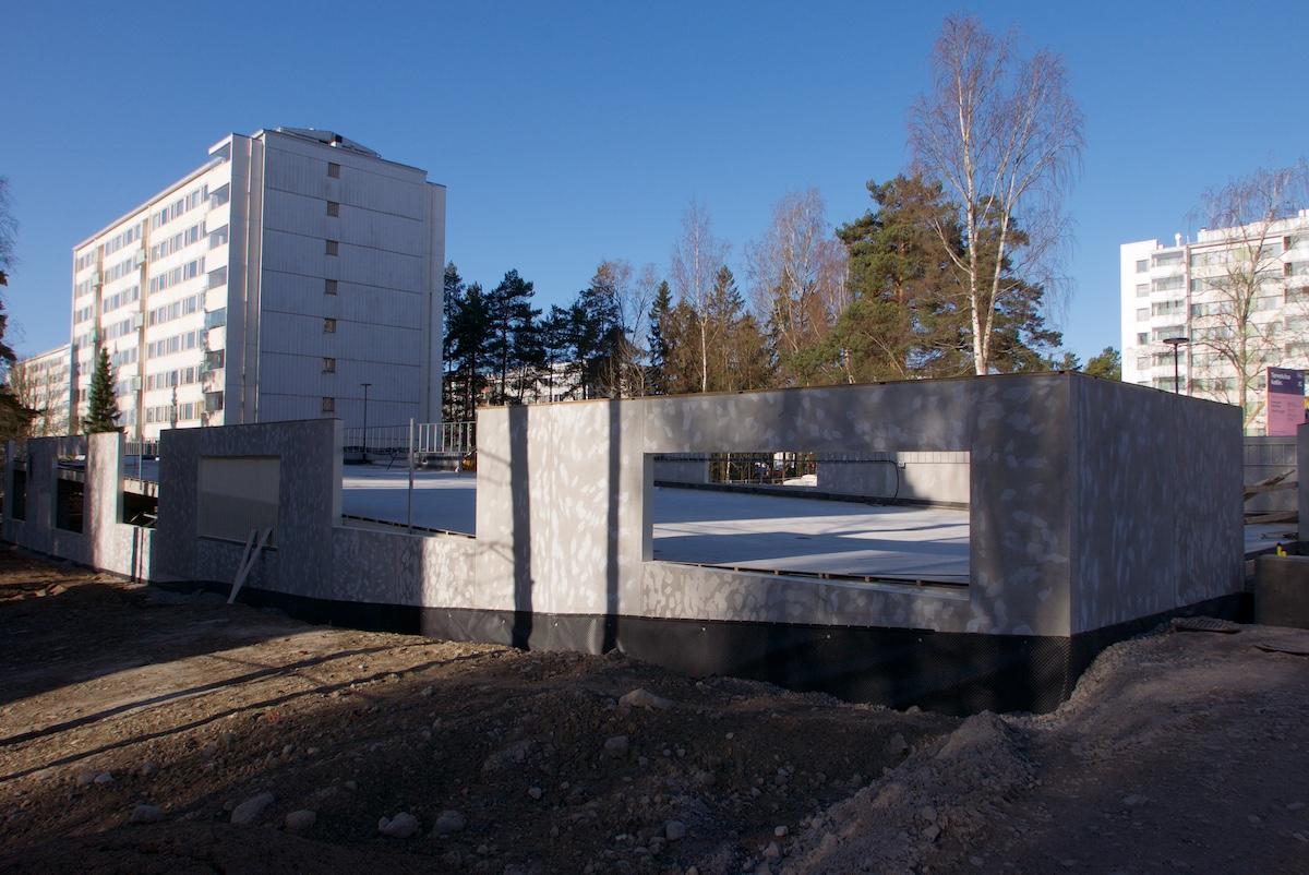 Pysäköintilaitosta rakennetaan, taustalla seitsenkerroksisia asuintaloja, koivuja ja mäntyjä