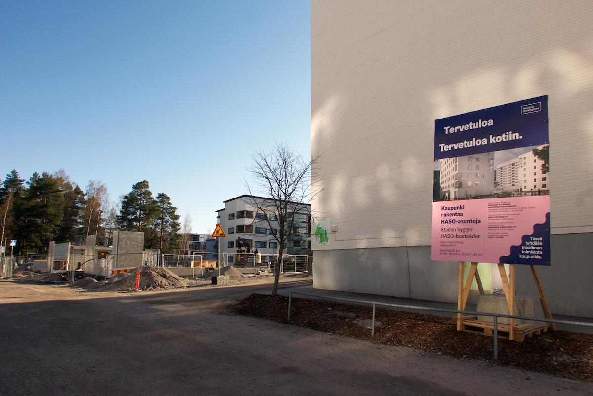 """Työmaan esittelytaulu, jossa piirros uusista taloista ja teksti """"Tervetuloa. Tervetuloa kotiin. Kaupunki rakentaa HASO-asuntoja."""" Taustalla uuden talon rakennustyömaa."""