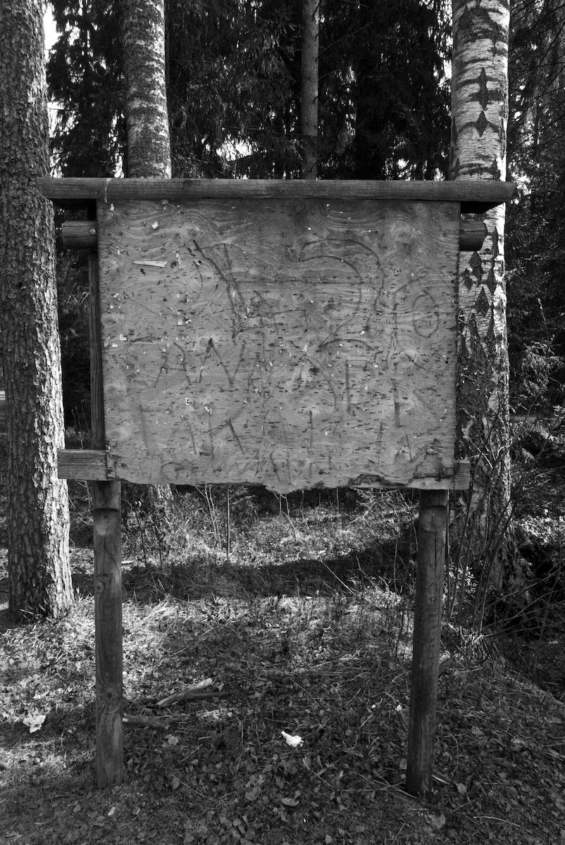 Metsän laidassa seisova vanha vanerinen ilmoitustaulu, jossa ei ole yhtään ilmoitusta mutta joka on täynnä vanhoja niittejä