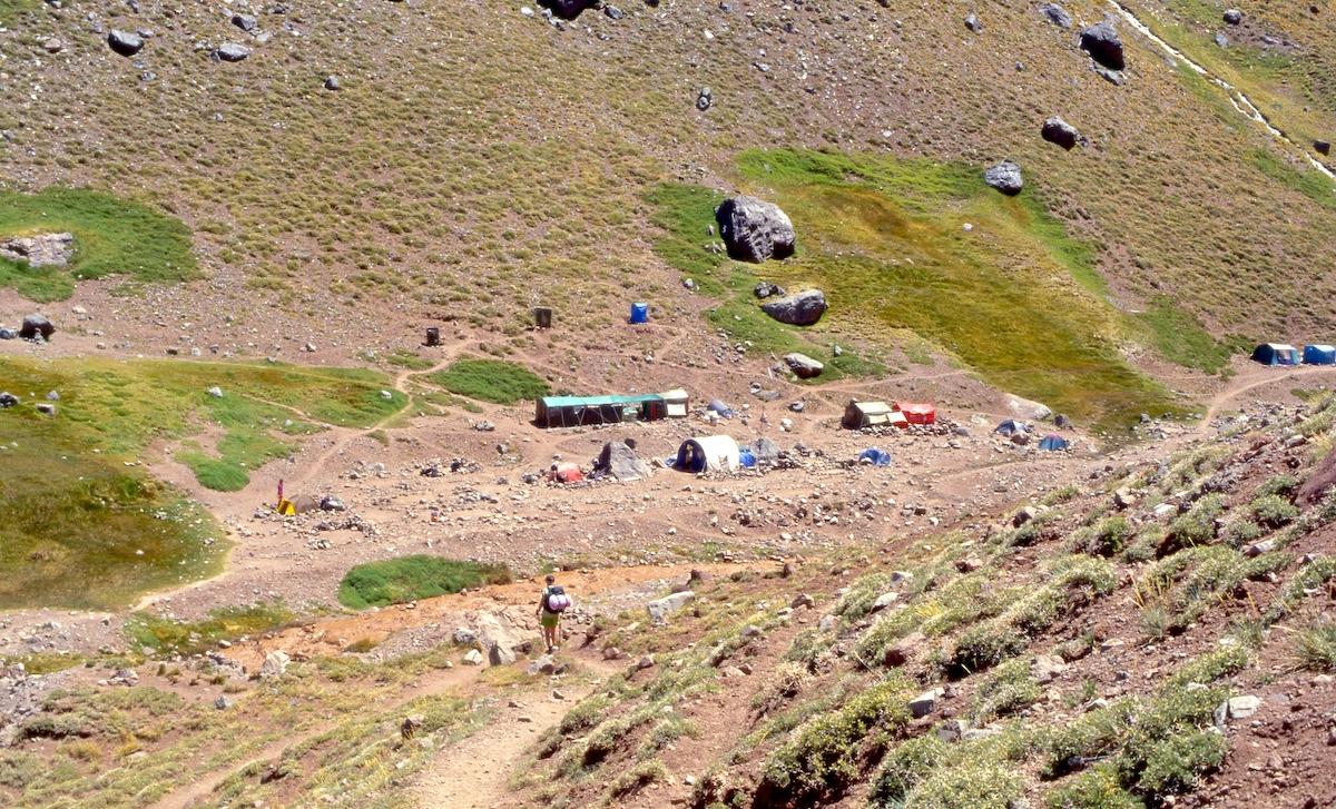 Jyrkkärinteisessä laaksossa leiri, jossa telttoja ja kivillä ympäröityjä teltanpaikkoja hiekkamaalla ruskeavetisen puron rannalla. Rinteellä kivenlohkareita, matalaa harvaa varvikkoa, kosteissa paikoissa sammalta ja ruohokasveja. Retkeilijä lähestyy leiriä ja ylittää kohta puron.